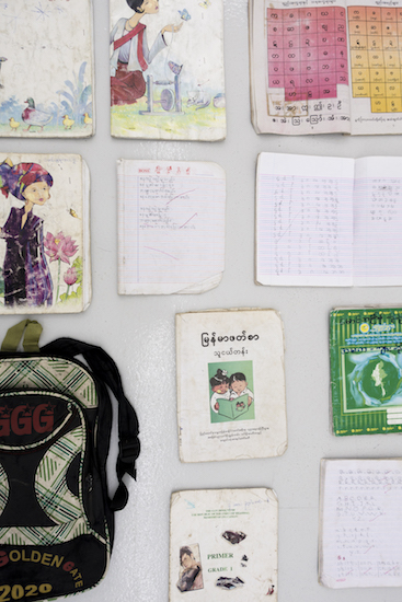 Detail of schoolbooks and schoolbags from installation Flying in the Fragmentary, 2016-18
